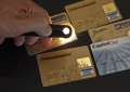 b6. Counterfeit payment cards. One card's hologram is being optically checked with a special magnifier